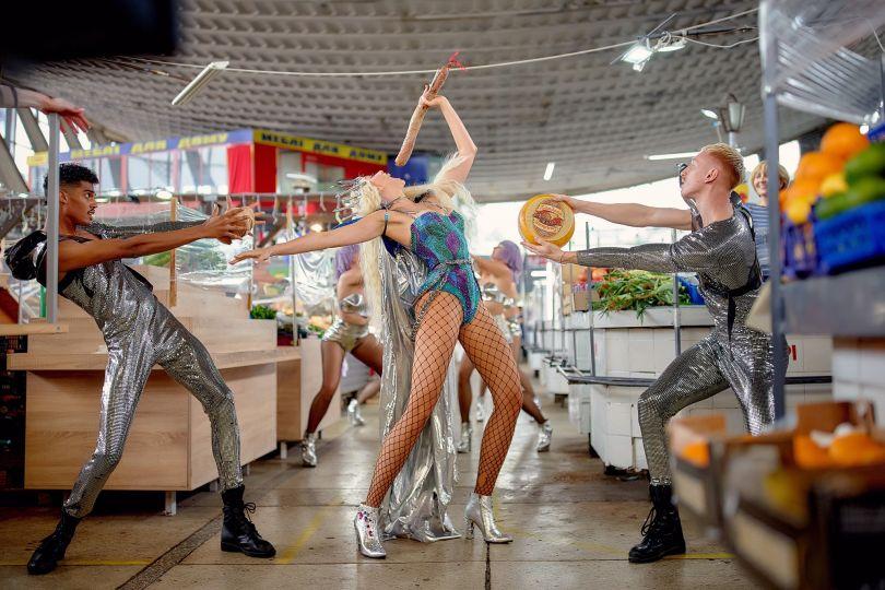 Оля Полякова співає з палкою ковбаси на Житньому ринку